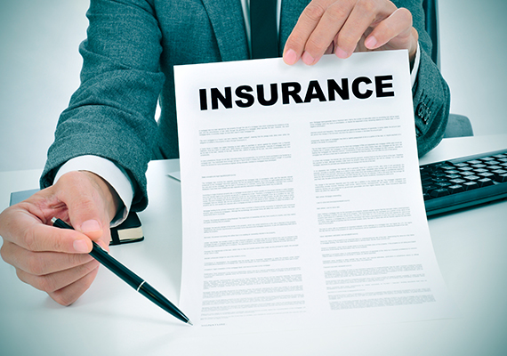Businessman holding insurance form and pen